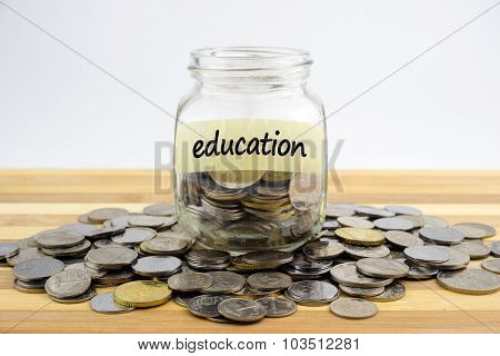 Coins In Glass Container With Education Label On Wooden Surface Against White Background.financial C