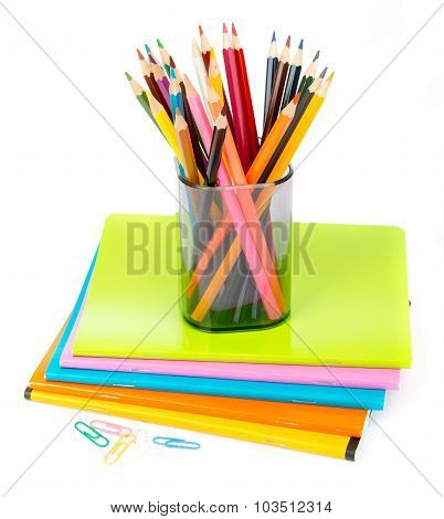 Pencil cup with crayons and clips on copybooks