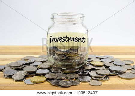 Coins In Glass Container With Investment Label On Wooden Surface Against White Background.financial