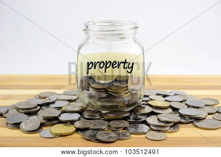 Coins In Glass Container With Property Label On Wooden Surface Against White Background.financial Co