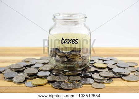 Coins In Glass Container With Taxes Label On Wooden Surface Against White Background.financial Conce