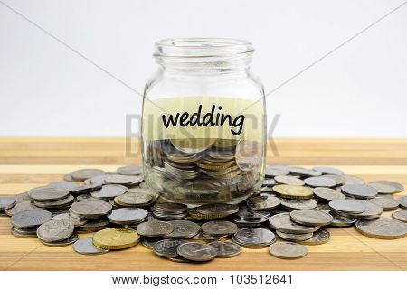 Coins In Glass Container With Wedding Label On Wooden Surface Against White Background.financial Con