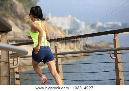fitness sports woman running on wooden boardwalk seaside
