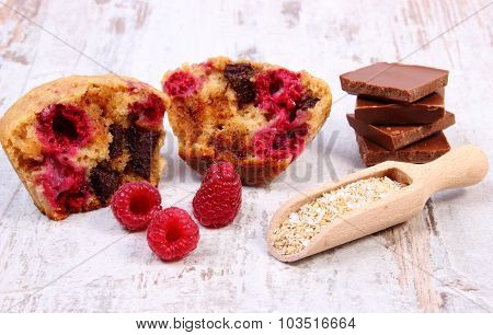 Muffins With Raspberries, Chocolate And Oat Bran On Spoon, Wooden Background, Delicious Dessert