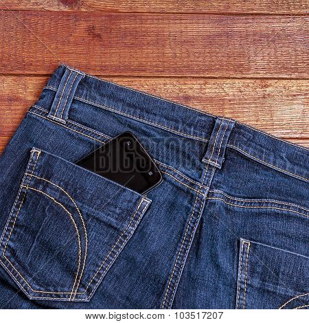 Smartphone In The Old Jeans Pocket On Wood Background