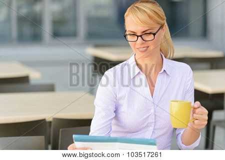 Pleasant businesswoman sitting at the table