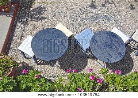 Two Round Tables With Soft Stools In Greece