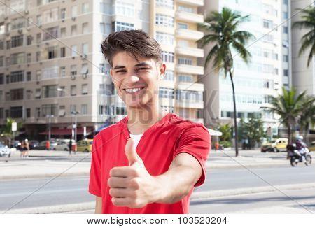 Laughing Hispanic Guy At City Showing Thumb Up