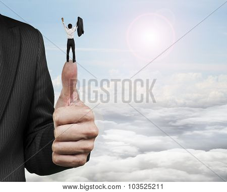 Businessman Cheering On Top Of Another Big Thumb