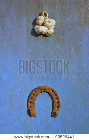 Sunlit Bunch Of Garlic And Horseshoe On Blue Background