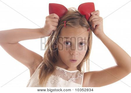 child hold red heart on her head on a white background