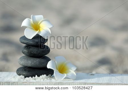 Spa stones with flowers on sand beach close up