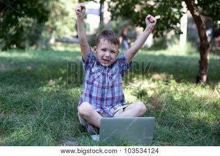 Little genius working on the computer, raising his hands screaming about success