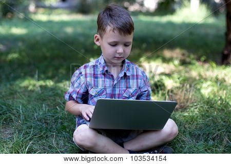 Little child is trained on the computer in the park on the grass