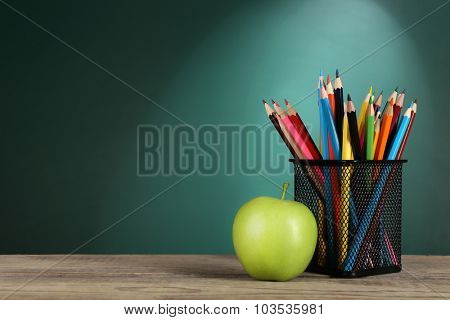 Green apple and metal cup with crayons on desk on green chalkboard background