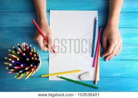 Hand with color pencils and blank sheet of paper on wooden table