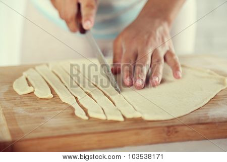 Woman making apple pie on wooden table, on light background