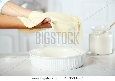 Woman making pie on wooden table, on light background