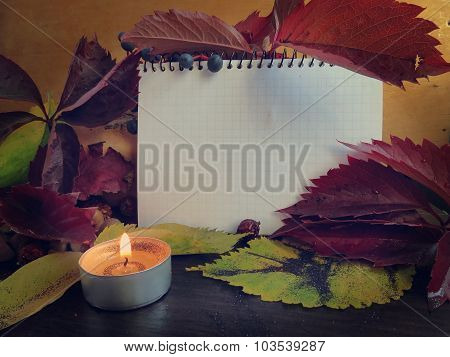 Notepad, autumn leaves with a candle on a dark surface