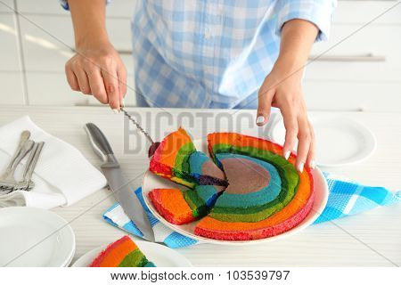 Young woman cutting rainbow cake in kitchen