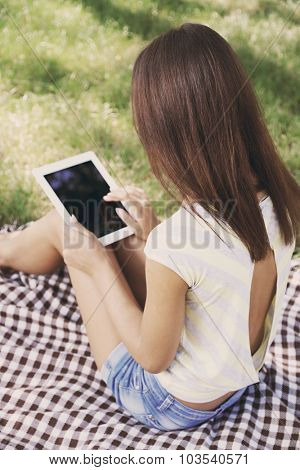 Beautiful young girl with tablet in park