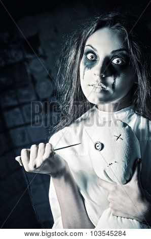 Horror Style Shot: Scary Crazy Girl With Moppet Doll And Needle In Hands