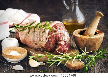 Raw Boneless Lamb Leg With Garlic And Rosemary On Wooden Background