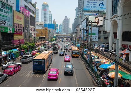 Typical Traffic With Buses, Taxis And Other Cars Along An Urban Street In Downtown Bangkok, Thailand