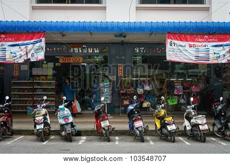 Typical Urban Storefronts In Krabi, Thailand, With Motorcycles Parked Curbside