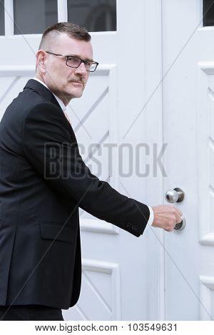 Man In Suit Standing At Door With Key