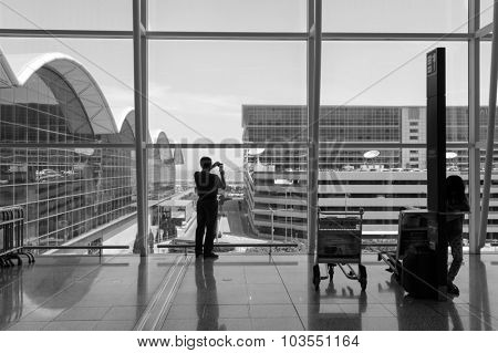 HONG KONG - JUNE 04, 2015: man taking photos in airport. Hong Kong International Airport is the main airport in Hong Kong. It is located on the island of Chek Lap Kok
