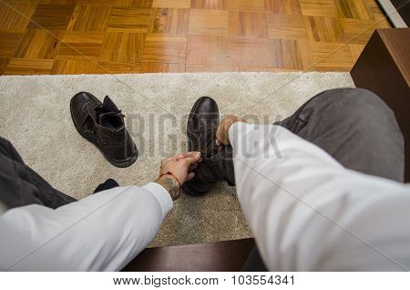 Man dressing tying his shoe laces