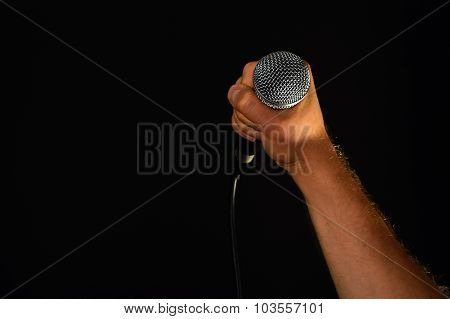 Male Hand With Microphone Isolated On Black