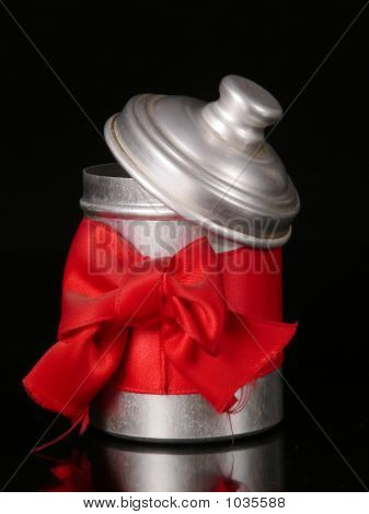 Tin With A Red Jib Around On A Black Background, Christmas Idea