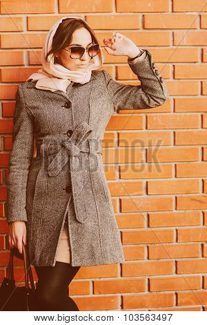 girl posing on a background of red brick wall