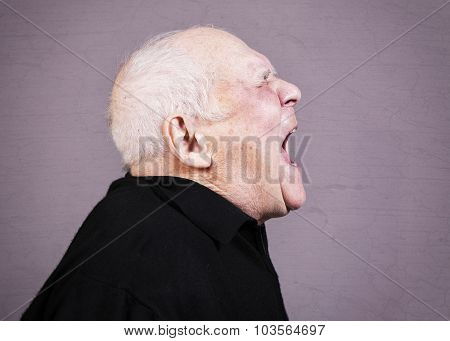 Profile photo of very emotional old man screams on a gray background