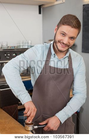 Attractive male worker is grinding brown seeds in cafe