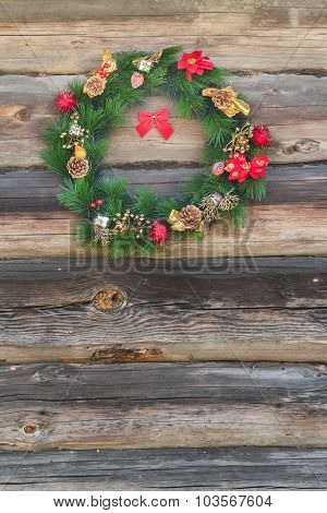 Outdoor X-mas Spruce Wreath At Old Log Cabin Wall Background