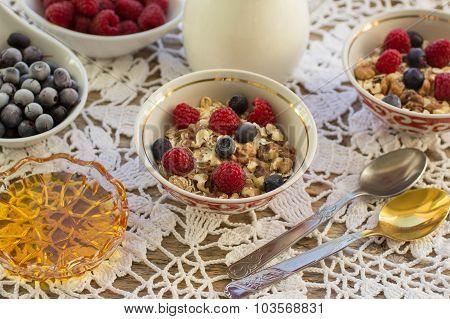 Homemade granola with raspberries, blueberries, walnuts and honey