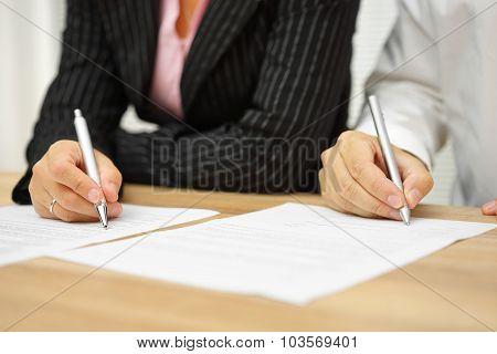 Businesswoman And Businessman Signing Contract In The Office