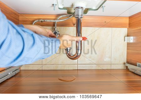 Plumber Is Repairing A Leaky Drain In Bathroom