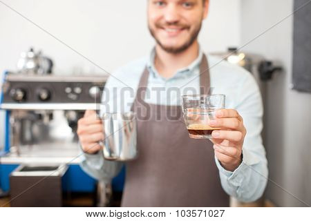 Handsome young barista is making coffee in cafeteria