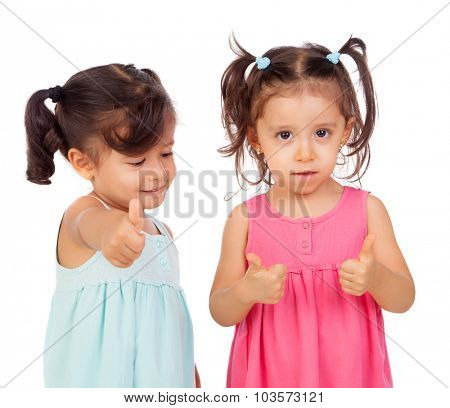 Twin sisters two years saying Ok isolated on a white background