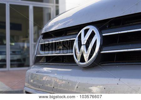 Car With Volkswagen Logo In Front Of Dealership Building