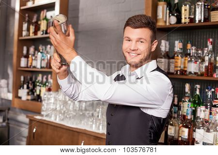 Attractive young male bartender is shaking cocktail