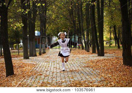Happy little schoolgirl run home from school, outdoor autumn park