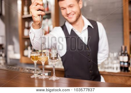 Handsome male bartender is making alcohol beverage