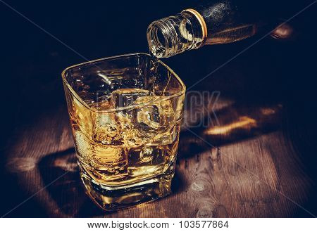 Barman Pouring Whiskey In The Glass On Wood Table, Warm Atmosphere, Old Style