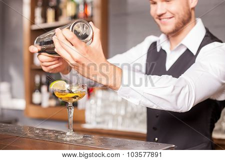 Attractive young male barman is preparing alcohol drink
