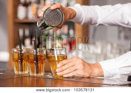 Professional male bartender is mixing drink in pub